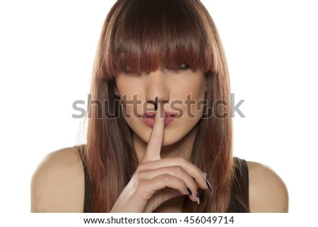 young woman with bangs his finger on his lips. silence gesture - stock photo