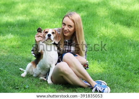 Young woman with beagle dog in green park