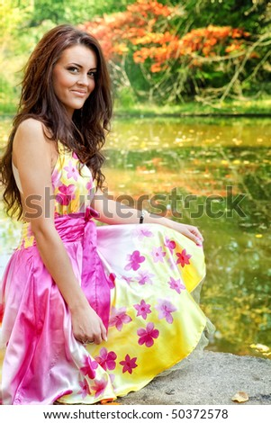 Young woman with beautiful colorful dress outdoor - stock photo