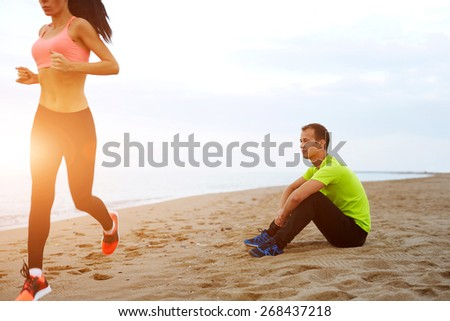 Young woman with beautiful figure running along the beach, couple working out against the sea at evening time, athletic man taking a break while his girlfriend exercising - stock photo