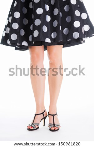 Young woman with beautiful legs standing in elegant black dress with white dots. Only the legs are visible. She is wearing glamorous high heels. - stock photo