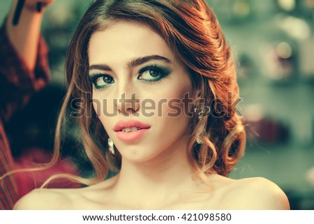 Young woman with beautiful makeup on face and stylish hairdo closeup