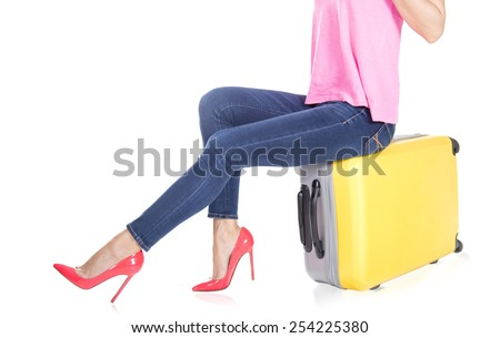 Young woman with beautiful smile standing with luggage isolated on white background - stock photo
