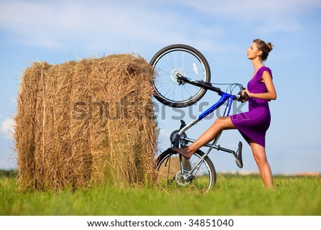 Young woman with bicycle at the field. Freaky concept.
