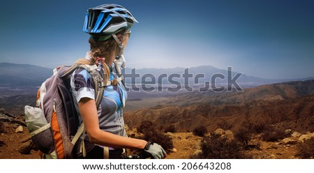 Young woman with bicycle standing in the desert mountains - stock photo