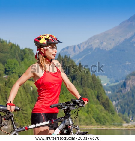 Young woman with bicycle standing in the mountains  - stock photo