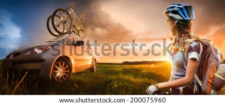 Young woman with bicycle standing in the mountains. Two bicycle on the roof of the car. - stock photo