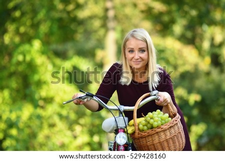 Young woman with bike in green park full of trees.