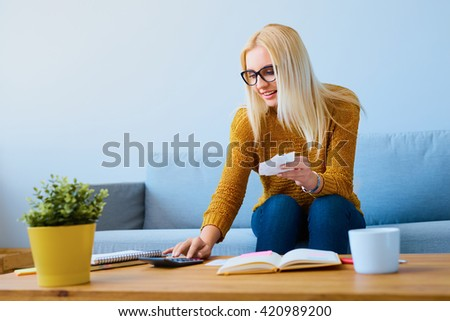 Young woman with bills calculating finances, sitting on sofa - stock photo