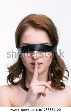 Young woman with black blindfold with finger over lips. Be quiet!!! - stock photo