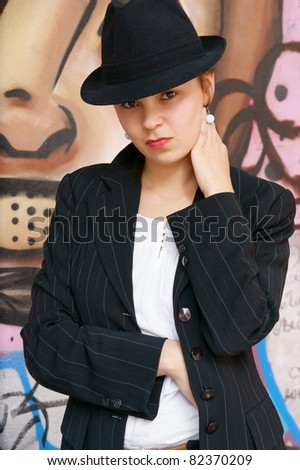 Young woman with black hat near color wall - stock photo
