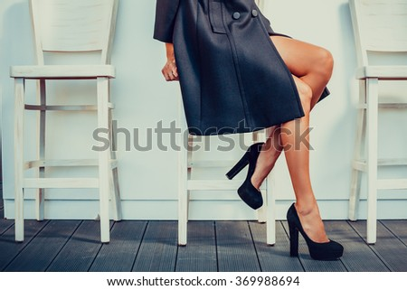 Young woman with black high heels shoes sitting on a chair and crossed her legs