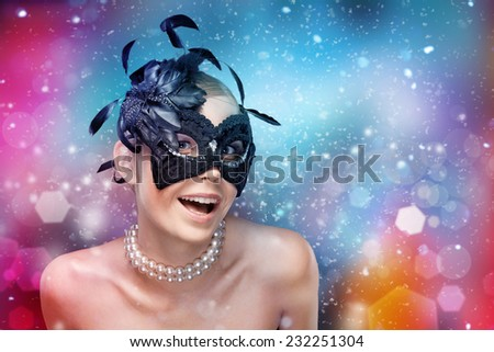 Young woman with black masquerade mask with feathers, fantasy background - stock photo