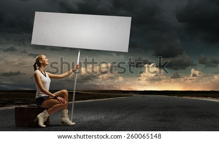 Young woman with blank banner sitting on suitcase - stock photo
