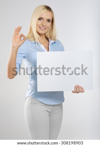 young woman with blank sign board and showing okay gesture
