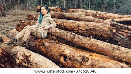 Young woman with blue hair sitting on stack of tree trunk, girl resting outdoor