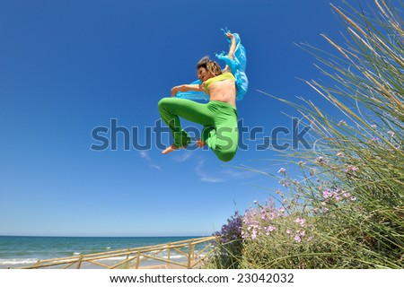 young woman with blue scarf jumping on the beach
