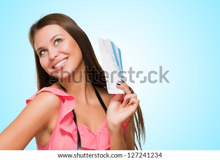 Young Woman With Boarding Pass And Camera against a blue background - stock photo