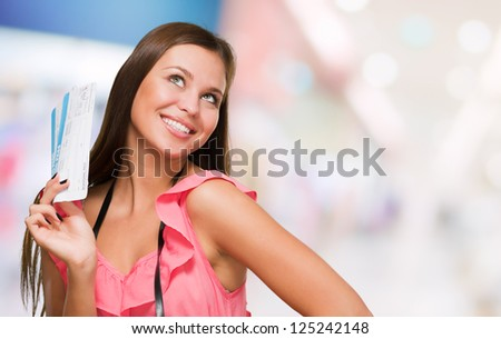Young Woman With Boarding Pass And Camera, indoor - stock photo