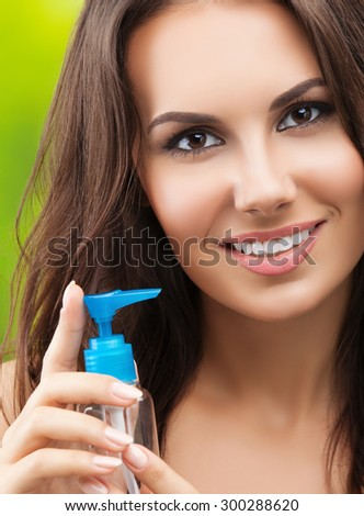 young woman with body lotion, outdoor - stock photo
