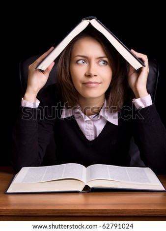 young woman with book at the table on black background - stock photo