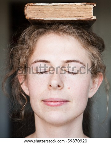 young woman with book on her head - stock photo