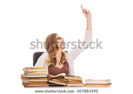Young woman with books pile pointing up