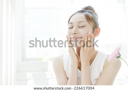 Young woman with both hands on her cheeks