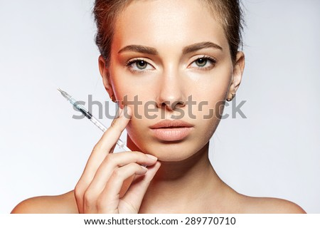 Young woman with Botox injections in the syringe on white background - stock photo
