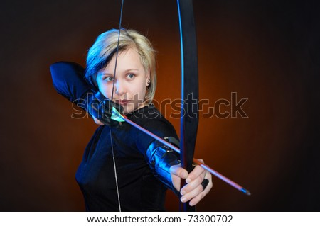 Young woman with bow and arrows, studio shot - stock photo