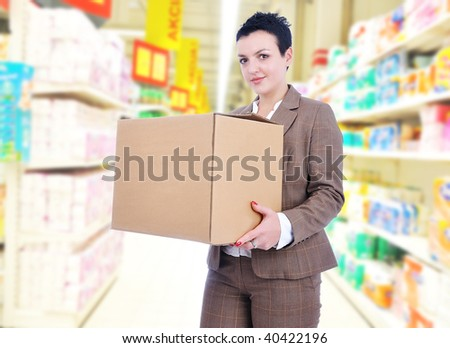Young woman with box in supermarket - stock photo