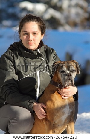 young woman with boxer dog on a winter day - stock photo