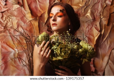 young woman with bright creative make up holding green flowers