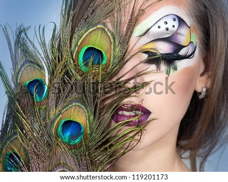 young woman with bright make up and peacock feather
