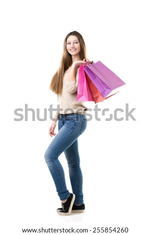Young woman with broad smile holding heap of shopping bags - stock photo