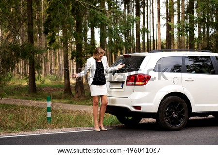 Young woman with broken car in the middle of forest
