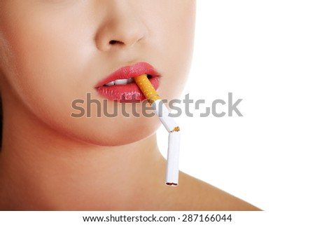 Young woman with broken cigarette in mouth. - stock photo