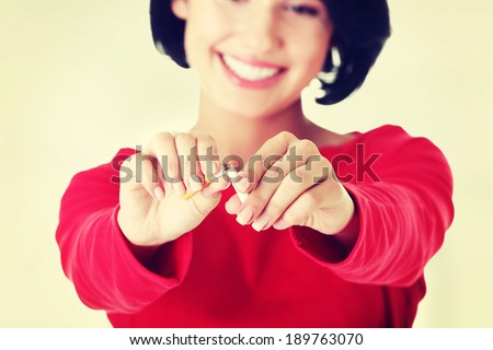 Young woman with broken cigarette. Stop smoking concept.  - stock photo