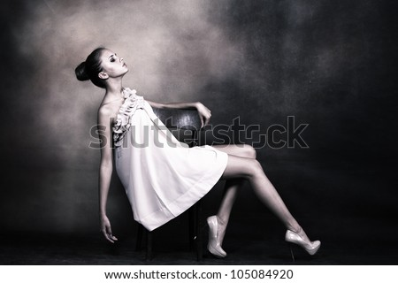 young woman with bun styled hair in elegant dress pose on chair, studio shot - stock photo