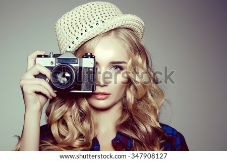 Young woman with camera. Blonde in a plaid shirt. Hipster fashion photographer girl. Young people, youth culture