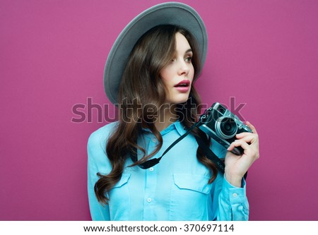 Young woman with camera. Brunette in a blue shirt. Hipster fashion photographer girl. Young people, youth culture
