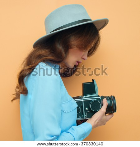 Young woman with camera. Brunette in a blue shirt. Hipster fashion photographer girl. Young people, youth culture - stock photo