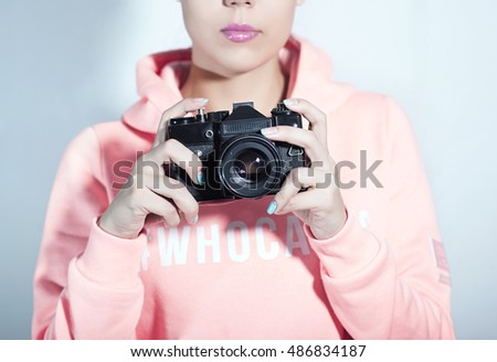 Young woman with camera. Brunette in a pink shirt. Hipster fashion photographer girl. Young people, youth culture