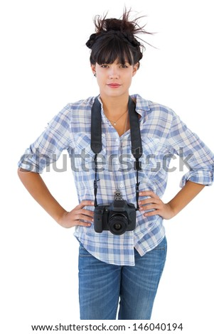 Young woman with camera put hands on her hips on white background - stock photo