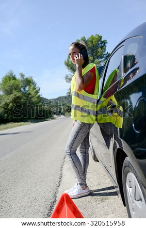 young woman with car breakdown on the roadside calling insurance company for assistance