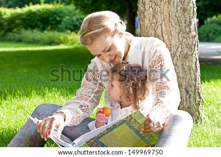 Young woman with child (daughter) in park read book - stock photo