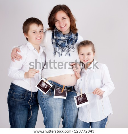 Young woman with children showing sonogram of her unborn child