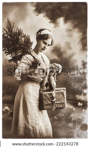 young woman with christmas tree and gifts, antique picture with original scratches and film grain - stock photo
