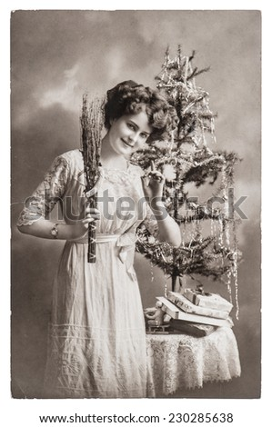 young woman with christmas tree and gifts. antique picture with original scratches and film grain  - stock photo
