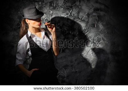Young woman with cigar on grey wall - stock photo